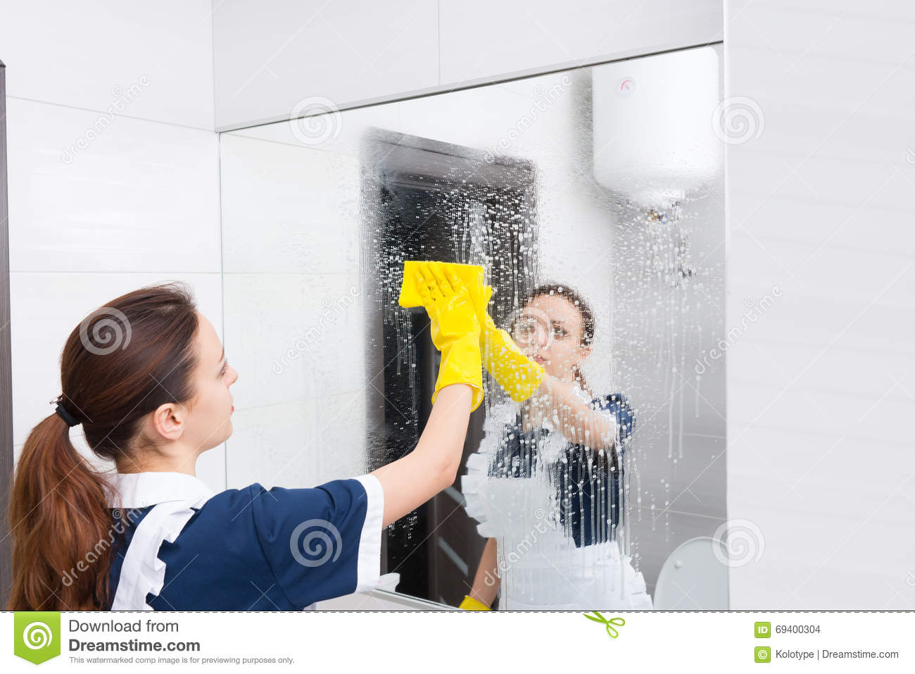 Housekeeper or maid cleaning a large wall mirror