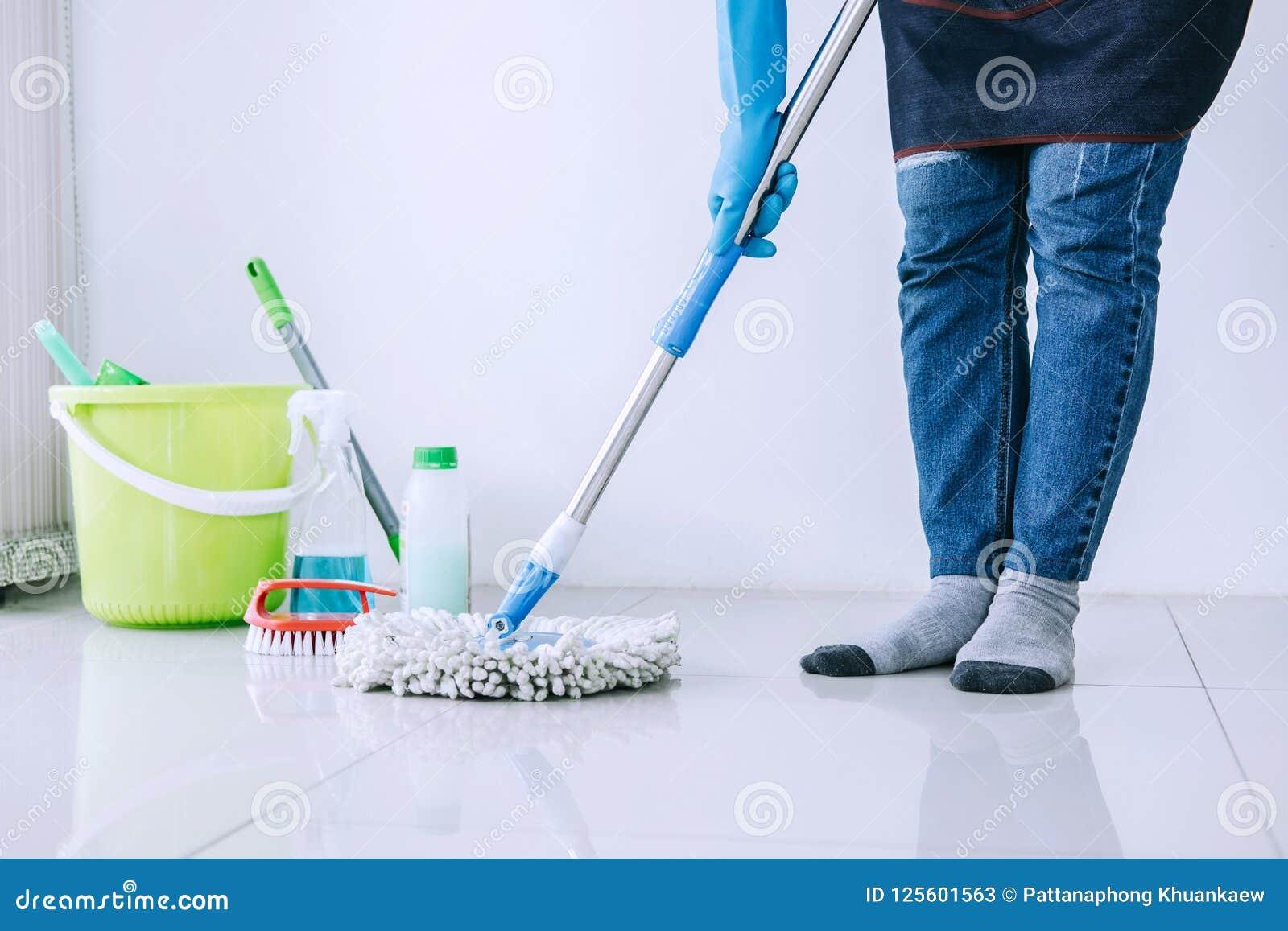 Housekeeping i cleaning pojęcie, Szczęśliwa młoda kobieta w błękitnym pocieraniu