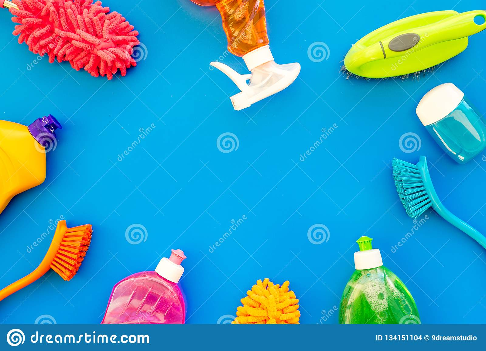 Housekeeping set. Detergents, soap, cleaners and brush for housecleaning on blue background top view mock-up