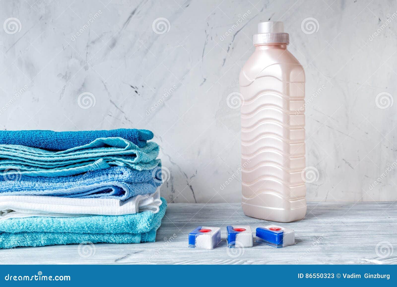 Housekeeping ustawiający z ręcznikami i klingeryt butelkami na pralnianym tło egzaminie próbnym