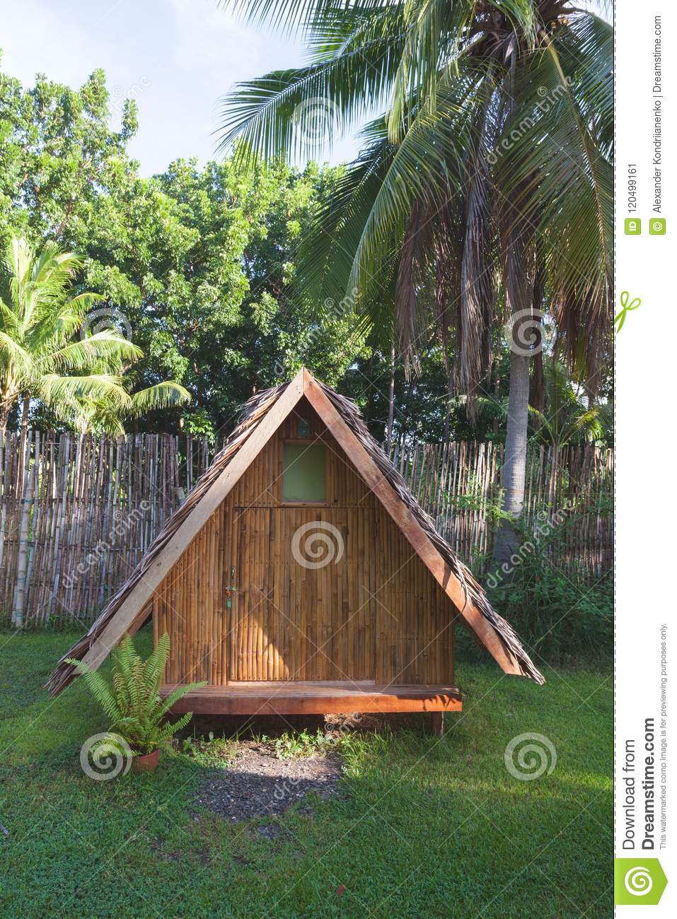 Houses made of wood. Bungalow with a roof made of palm leaves against the backdrop of a fence of bamboo and palm trees.