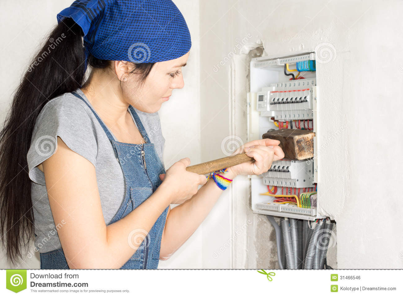 Housewife armed with a wooden mallet attacking an open electrical fuse box  in frustration as she tries to solve her problems