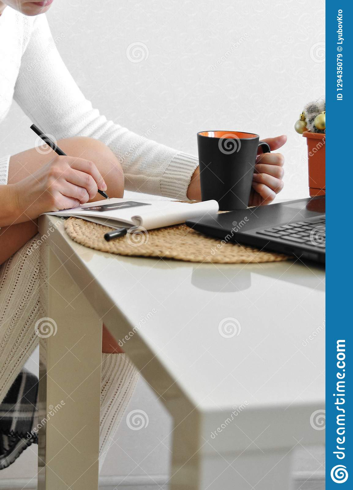 A housewife girl in a cozy white sweater and socks on a chair with a blanket works with a laptop in the kitchen. Online shopping w