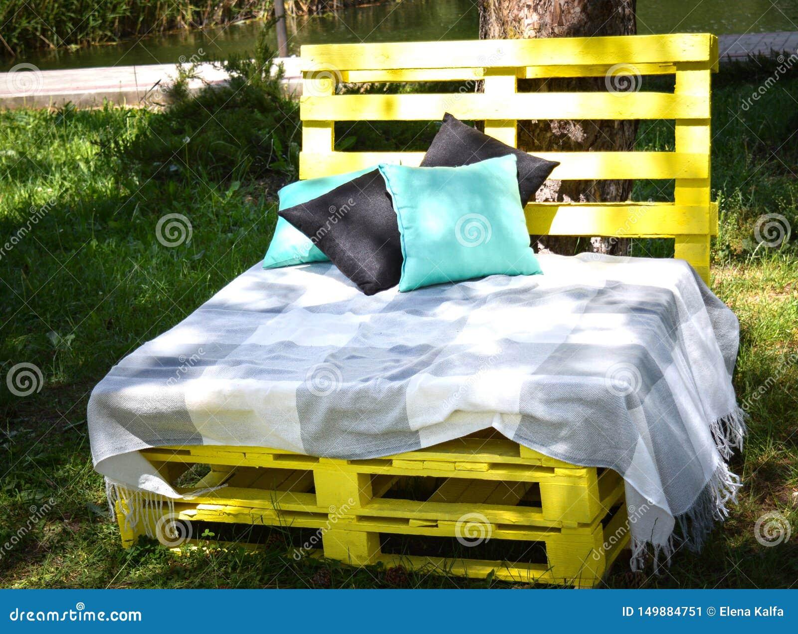 Houten bank die van gele pallets van de gevallen van de vrachtlading voor sittin met hoofdkussens en plaid in het park wordt gema