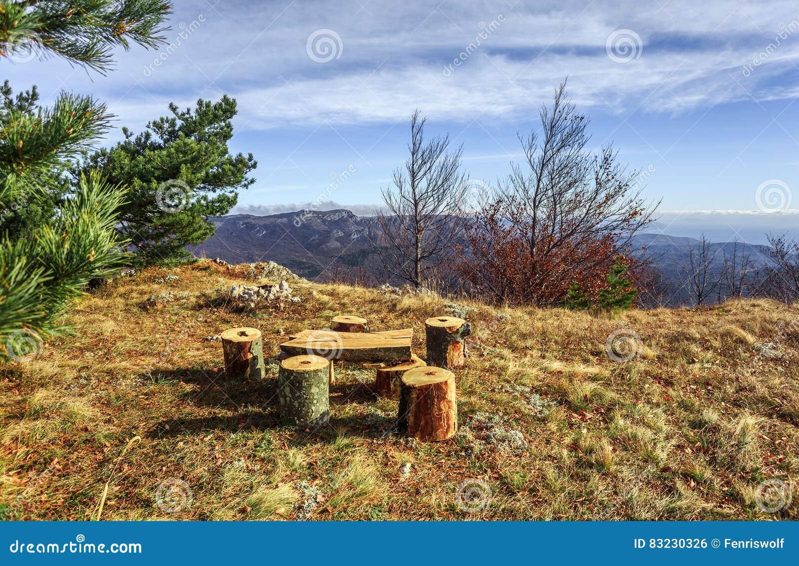 Houten banken, lijst en vuurplaats op de open plek dichtbij pijnboom RT
