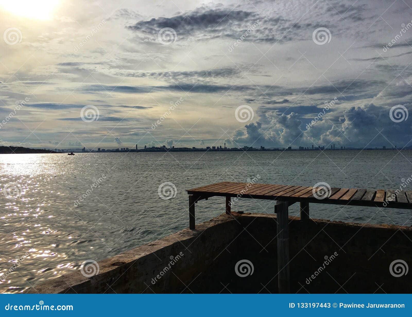 Houten brug aan de overzeese mening onder bewolkte hemel en zonneschijn