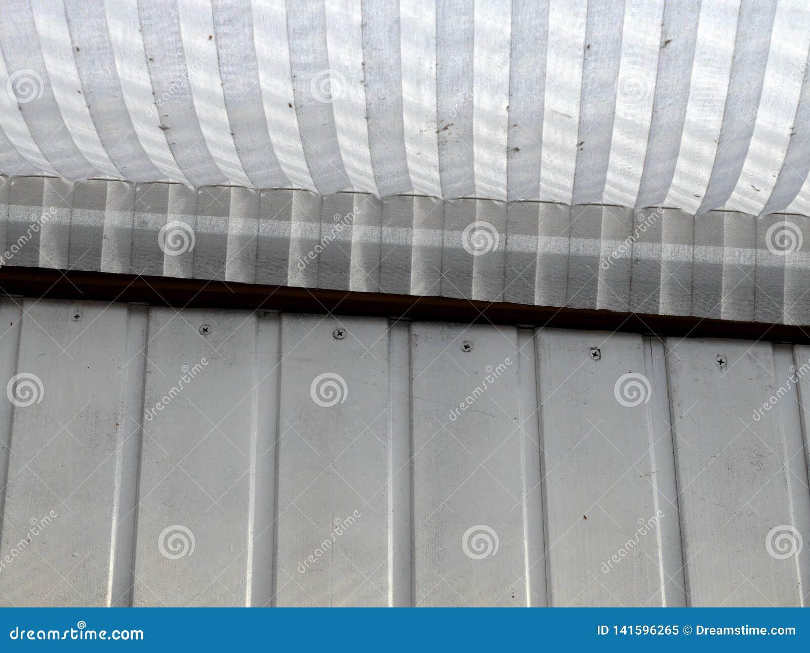 Houten houten buitenbekleding geschilderd wit met document geribbeld latblind