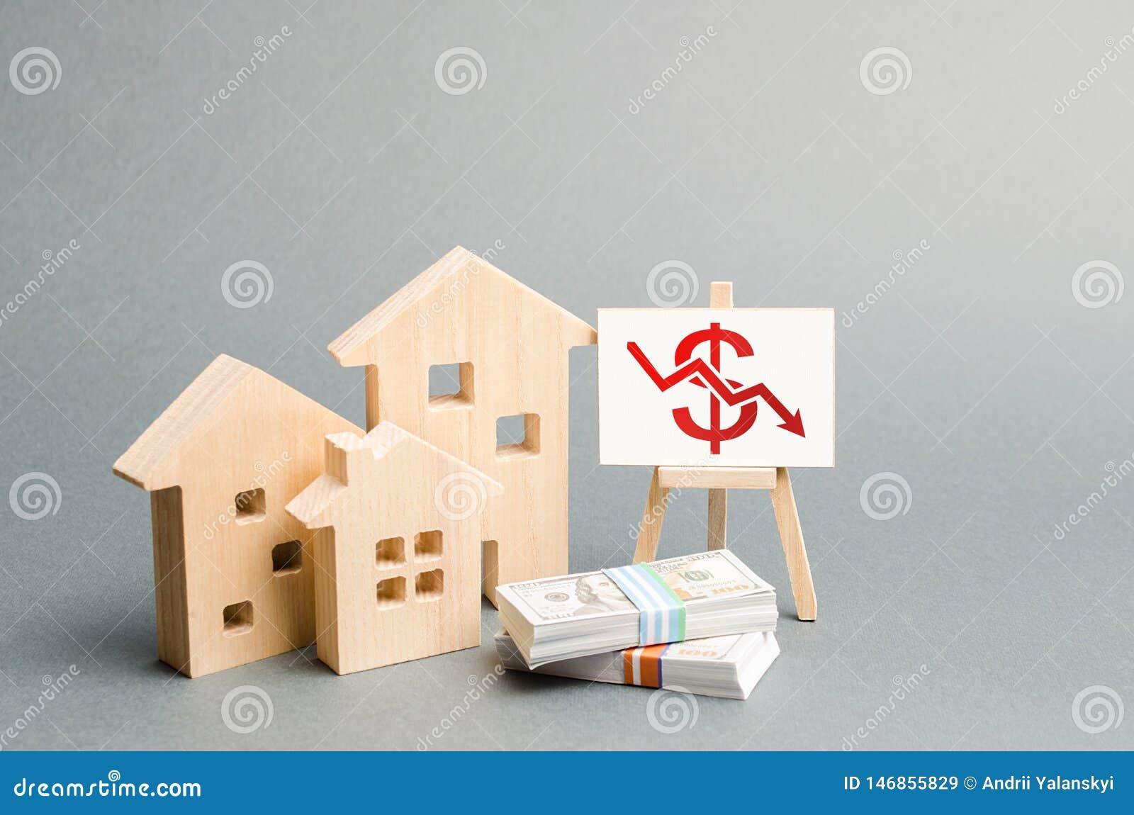 Houten cijfers van huizen en een affiche met een symbool van dalende waarde concept de daling van de onroerende goederenwaarde la