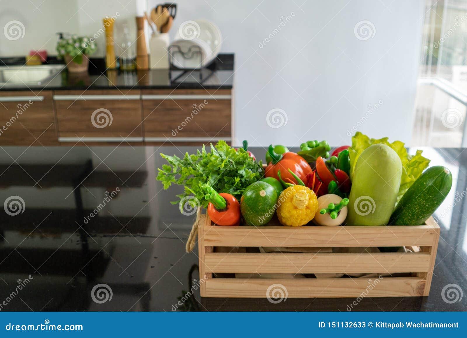 Houten die kratten met diverse soorten verse die groenten worden gevuld op de teller in de keuken worden geplaatst