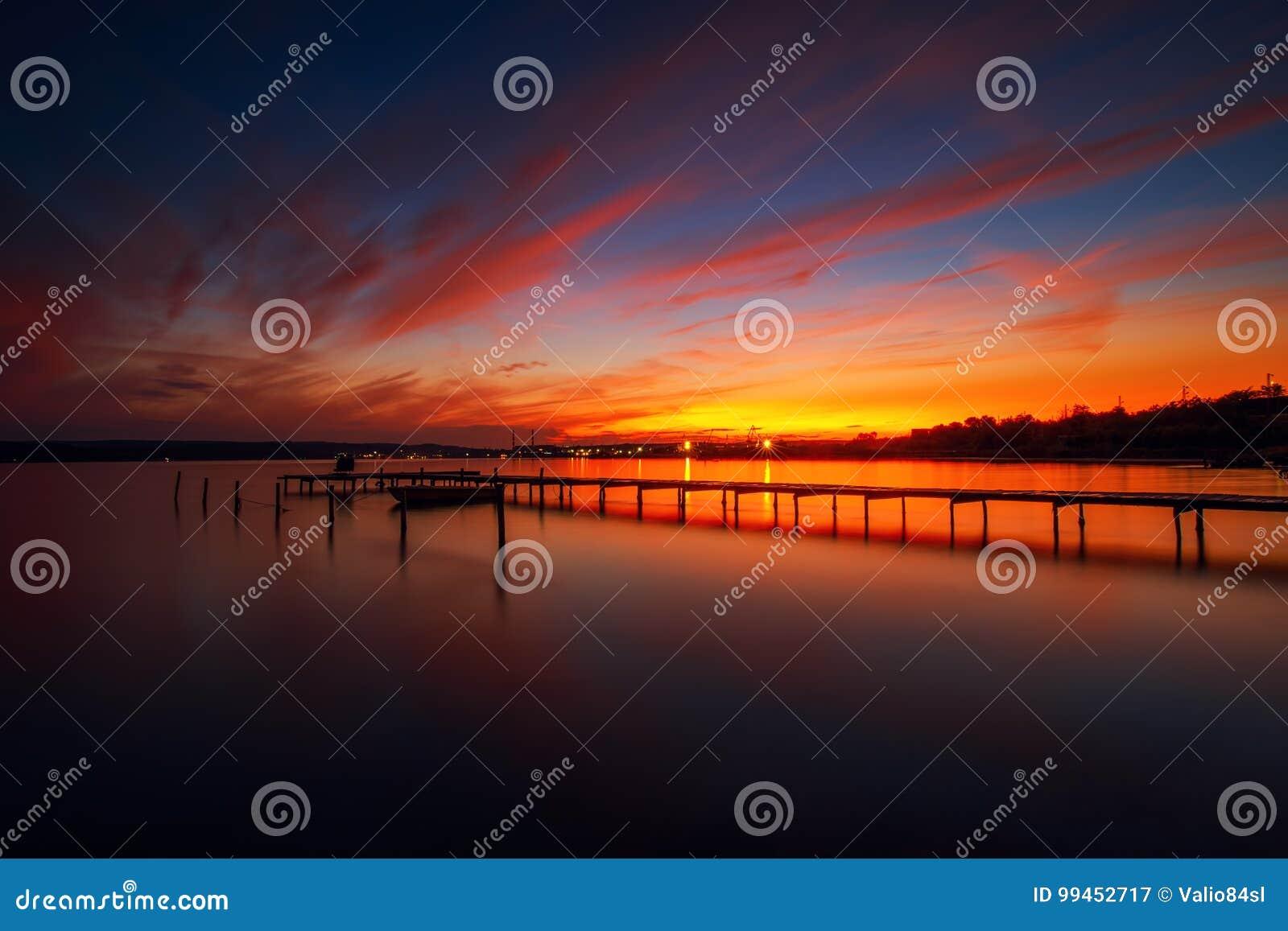 Houten Dok en vissersboot bij het meer, zonsondergangschot