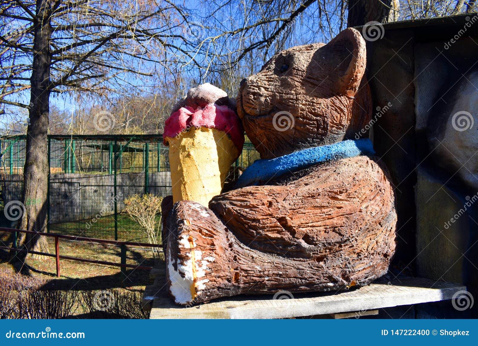 Houten draag pop etend roomijs in het park