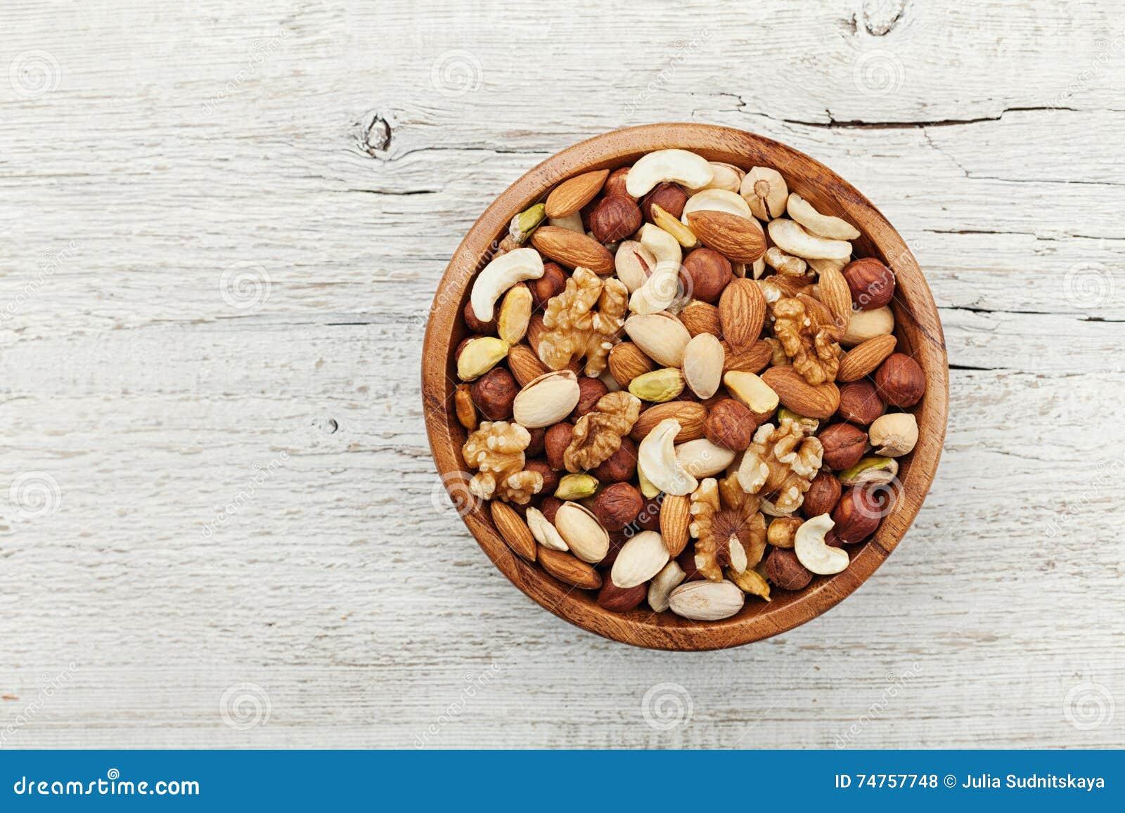 Houten kom met gemengde hierboven noten op witte lijst van Gezonde voedsel en snack Okkernoot, pistaches, amandelen, hazelnoten e