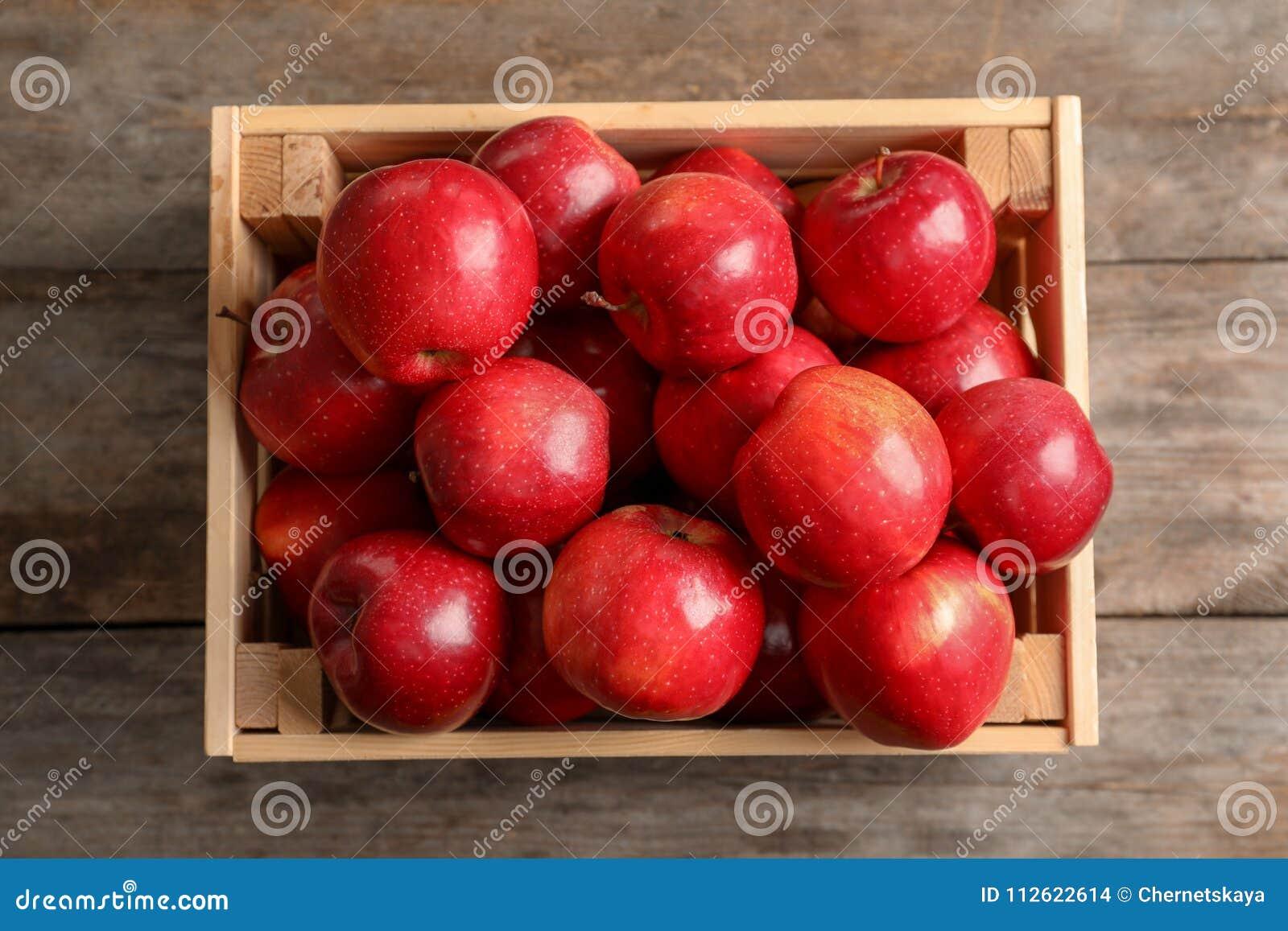 Houten krat met verse rode appelen op lijst