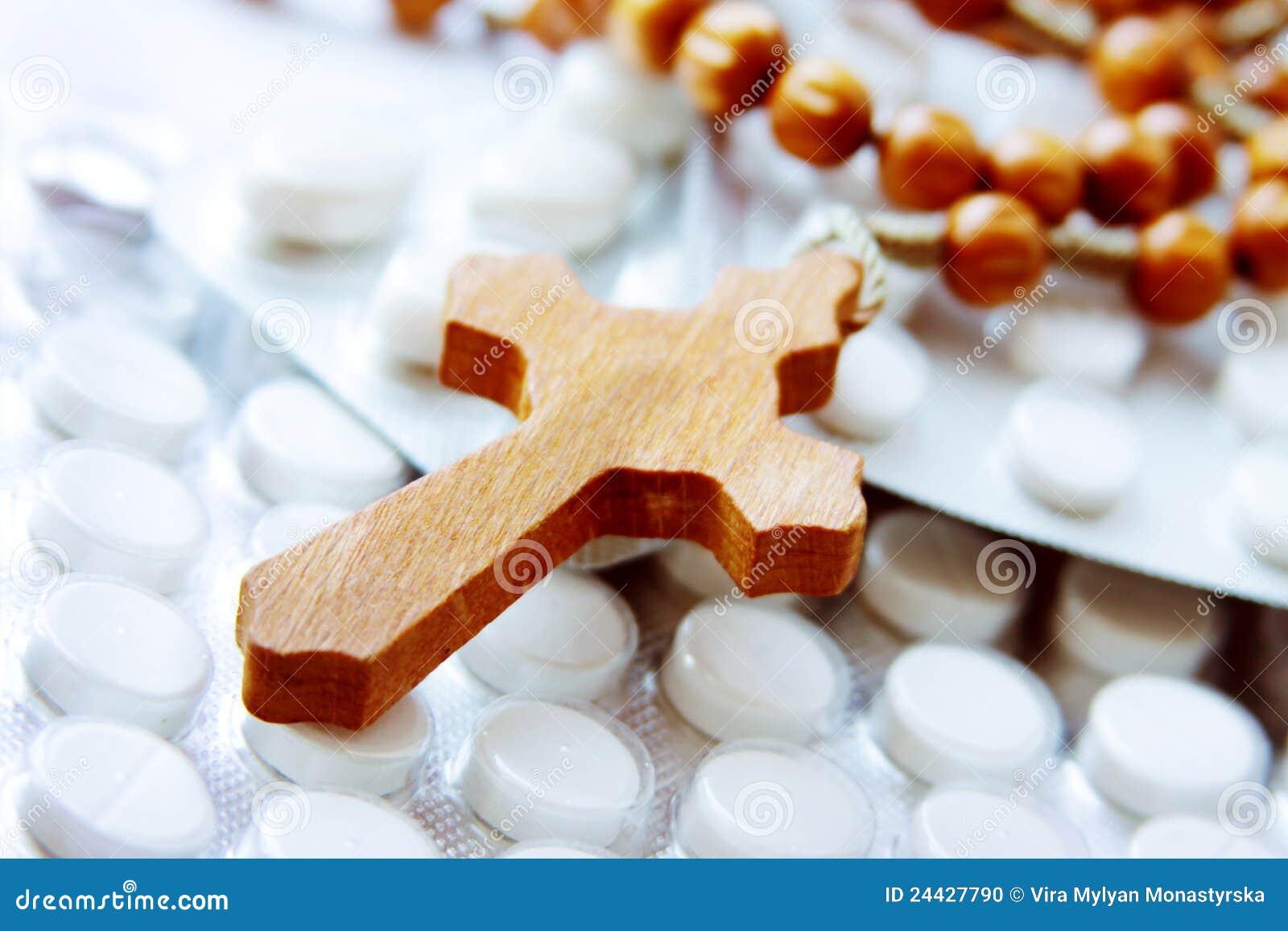 Houten kruis op pakketten van pillen