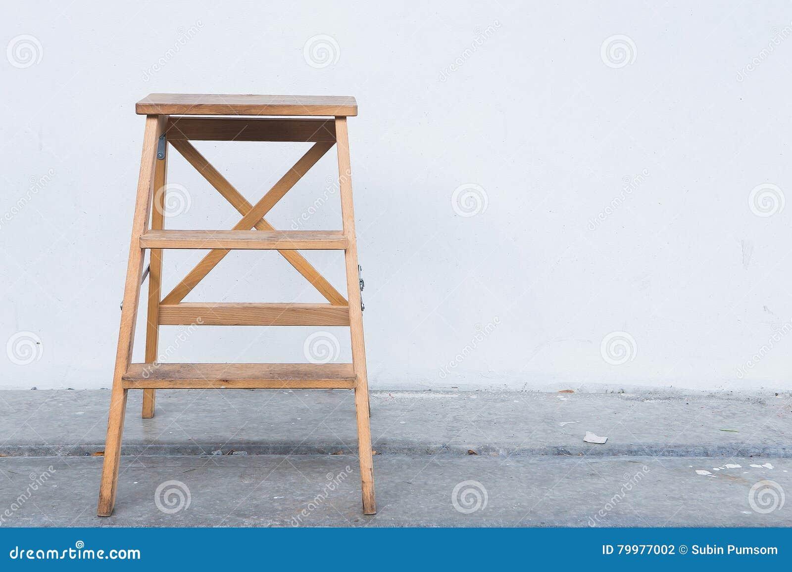 Houten ladder op witte muur met uitstekende houten vloer