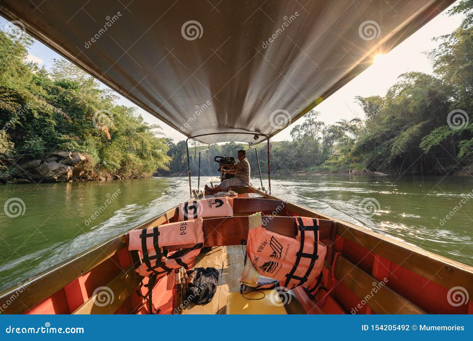 Houten lang-staartboot die in tropisch regenwoud op rivierkwai varen