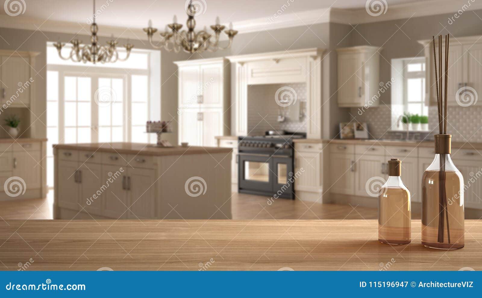 Houten lijstbovenkant of plank met aromatische stokkenflessen over vage klassieke keuken met eiland, witte architectuur binnenlan