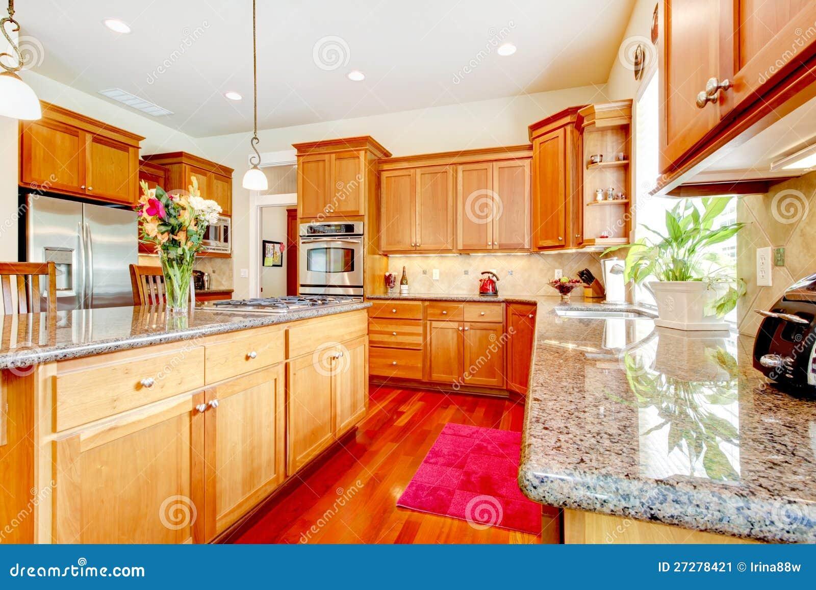 Houten luxe grote keuken met rood en graniet.