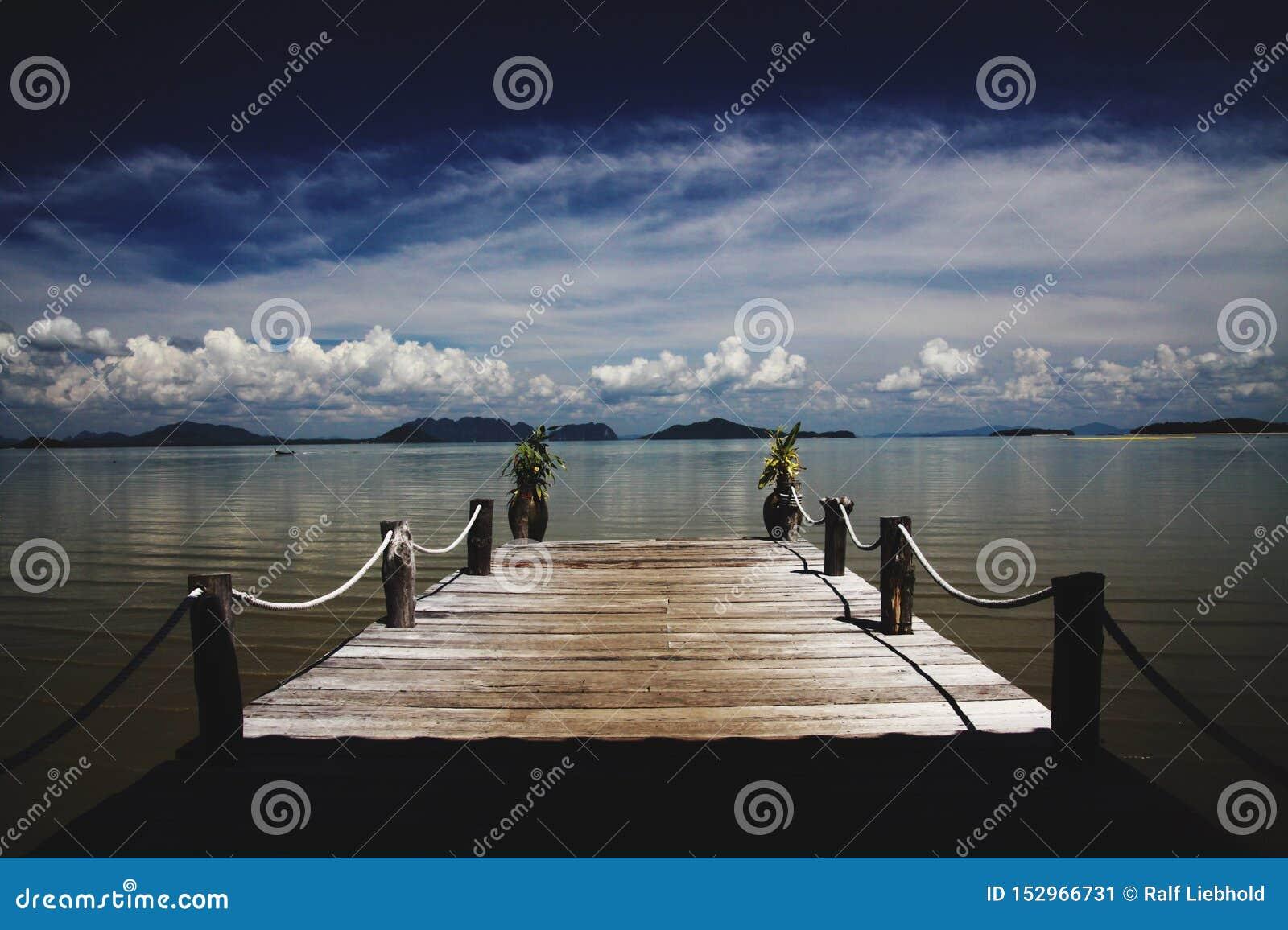 Houten pijler die in het Andaman-overzees op tropisch eiland Ko Lanta, Thailand leiden