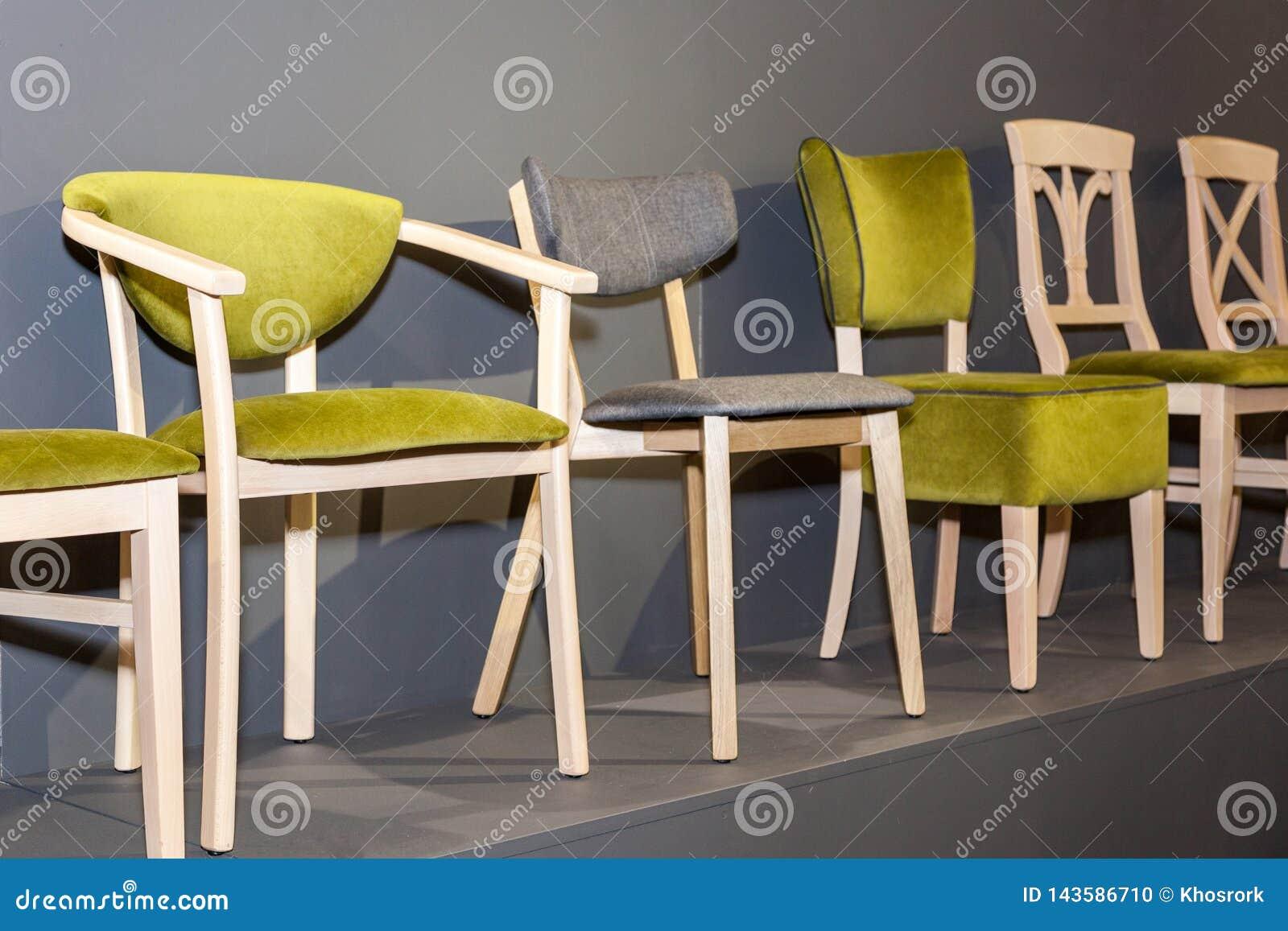 Houten stoelen met groen bekleed dichtbij grijze muur