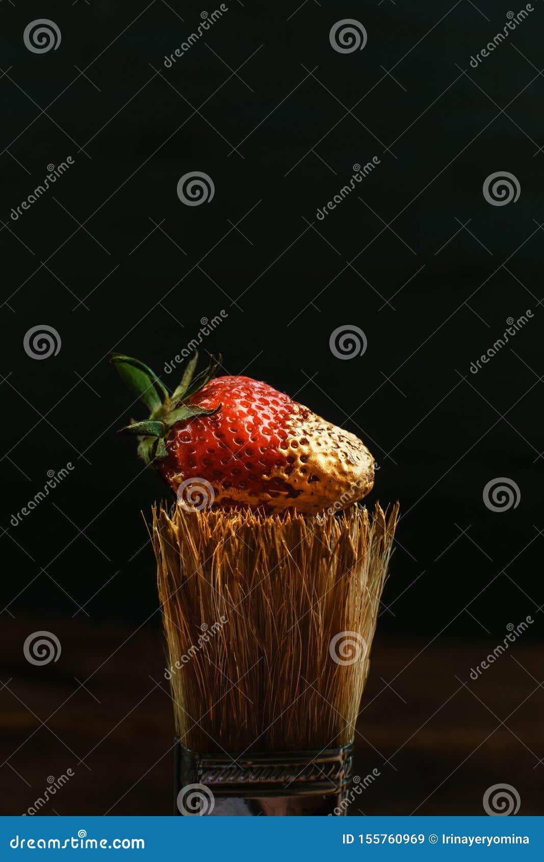 Houten varkenshaar het schilderen borstel met gouden verf en rode verse aardbei op zwarte achtergrond Donkere zeer belangrijke, m
