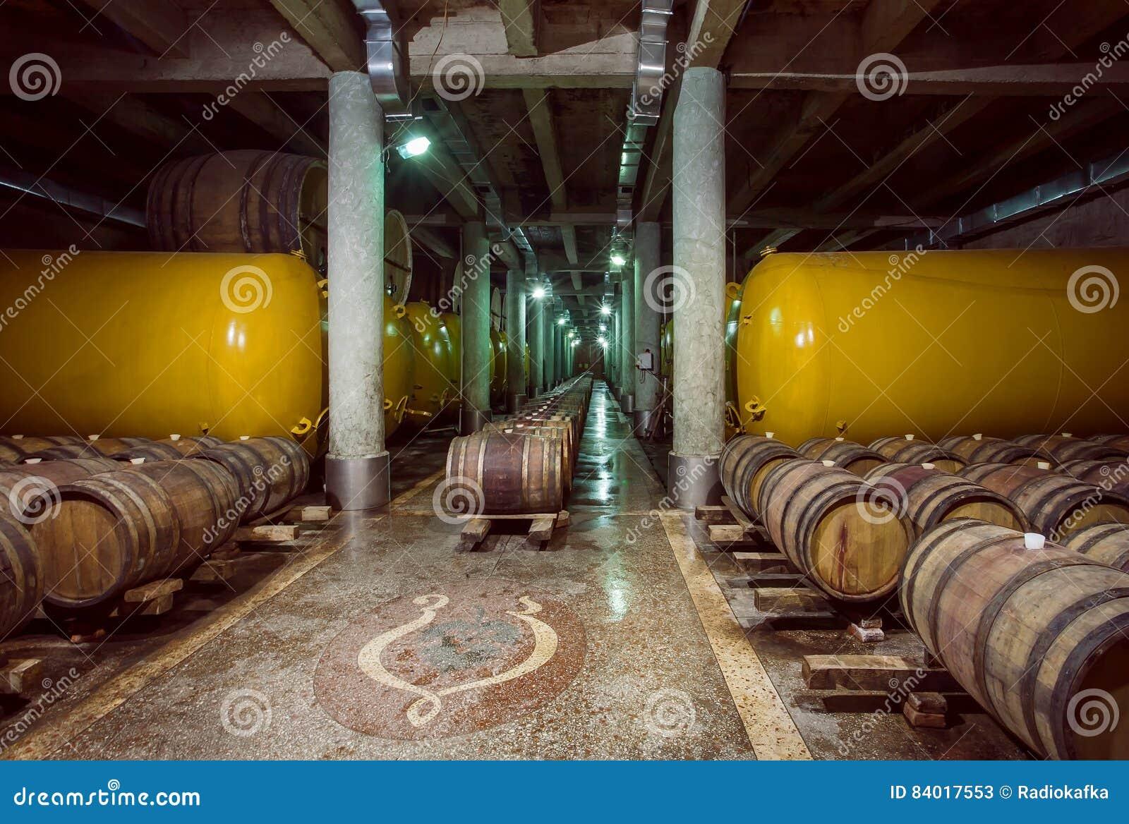 Houten vaten en metaalreservoir met wijn binnen oude kelder van