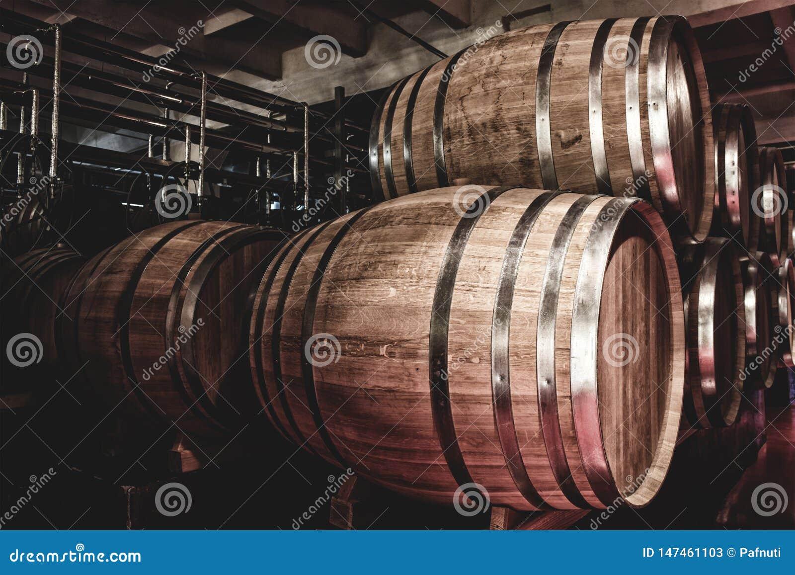 Houten vaten met whisky in donkere kelder