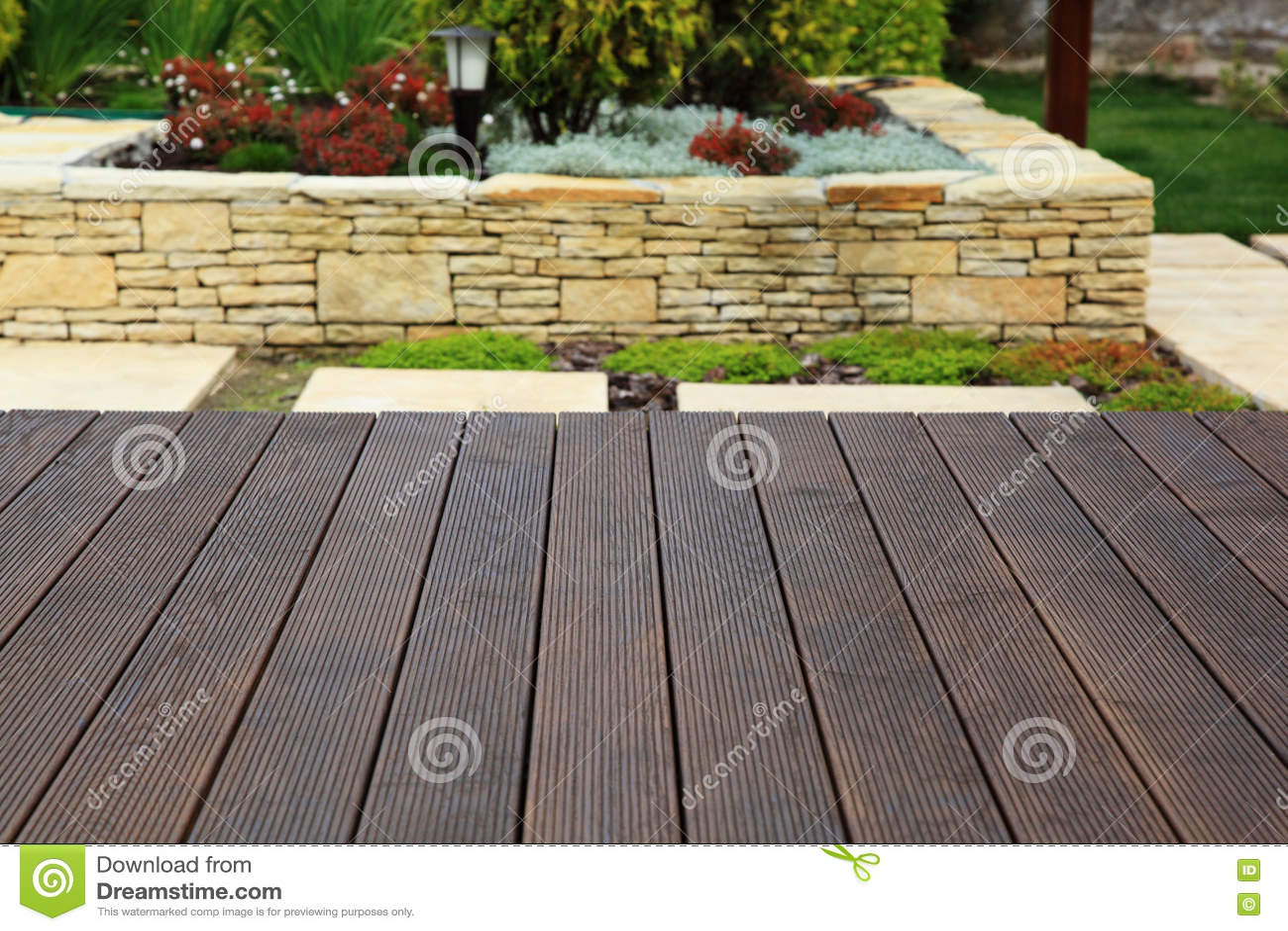 Houten vloer over mooie moderne decoratieve tuin als achtergrond