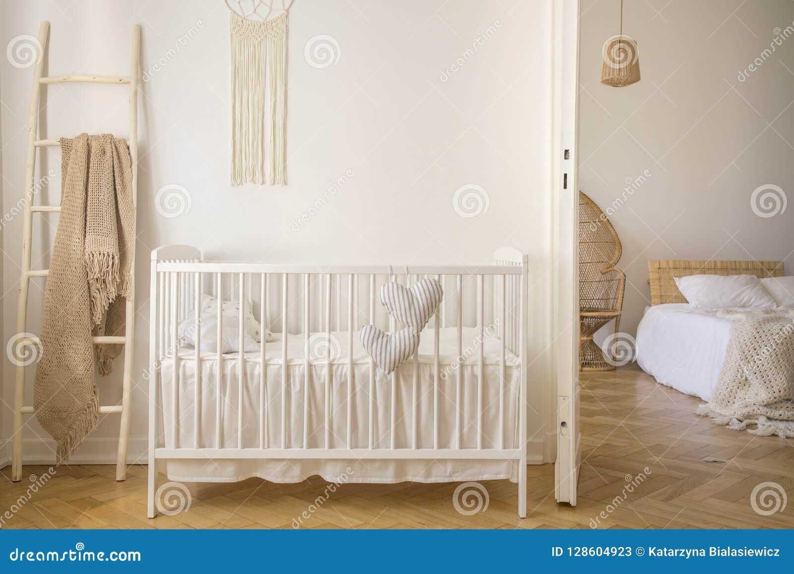 Houten voederbak met kussens die zich in echte foto van het witte binnenland van de jong geitjeruimte met deken op ladder bevinde