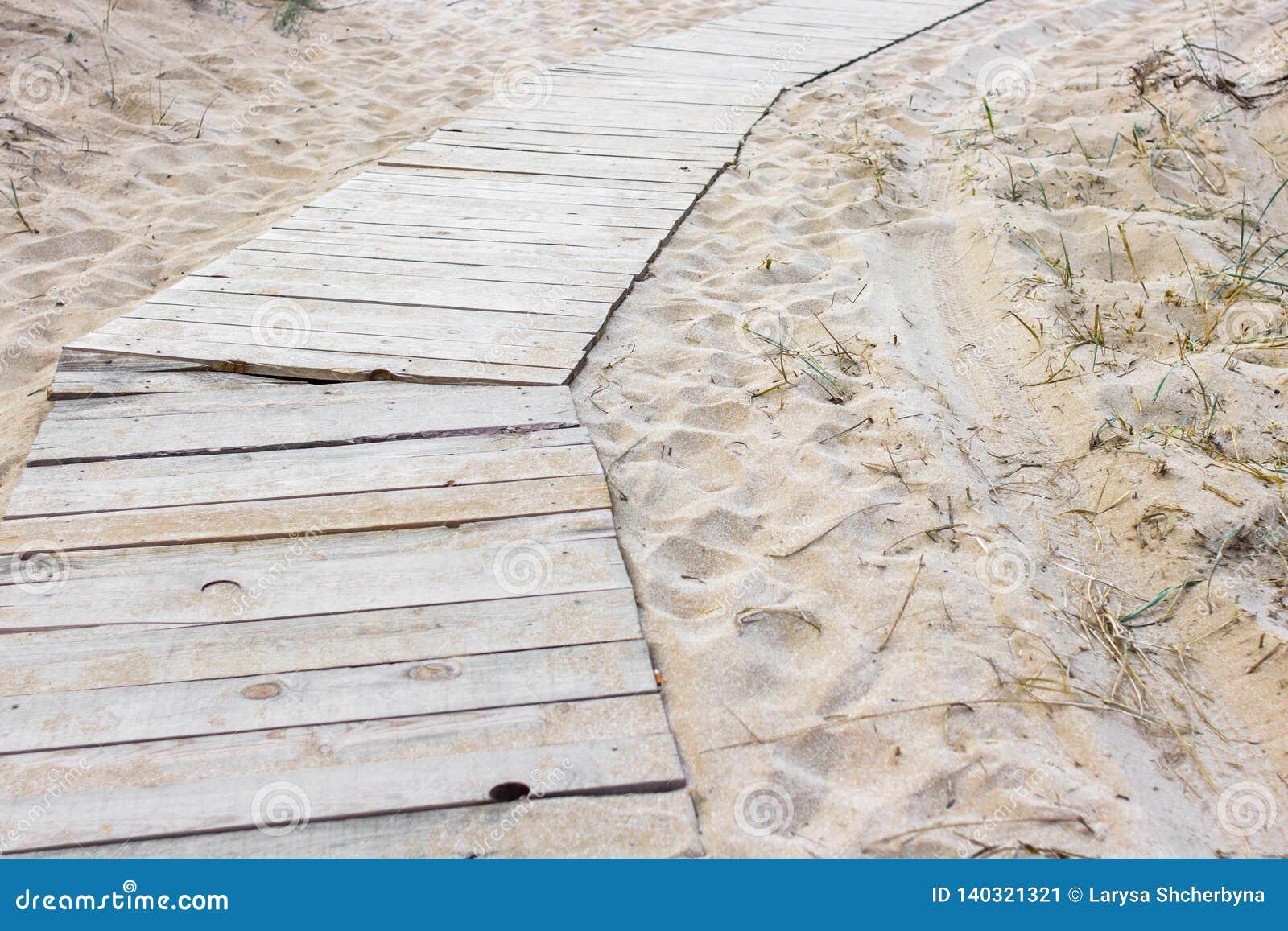 Houten weg onder het zand