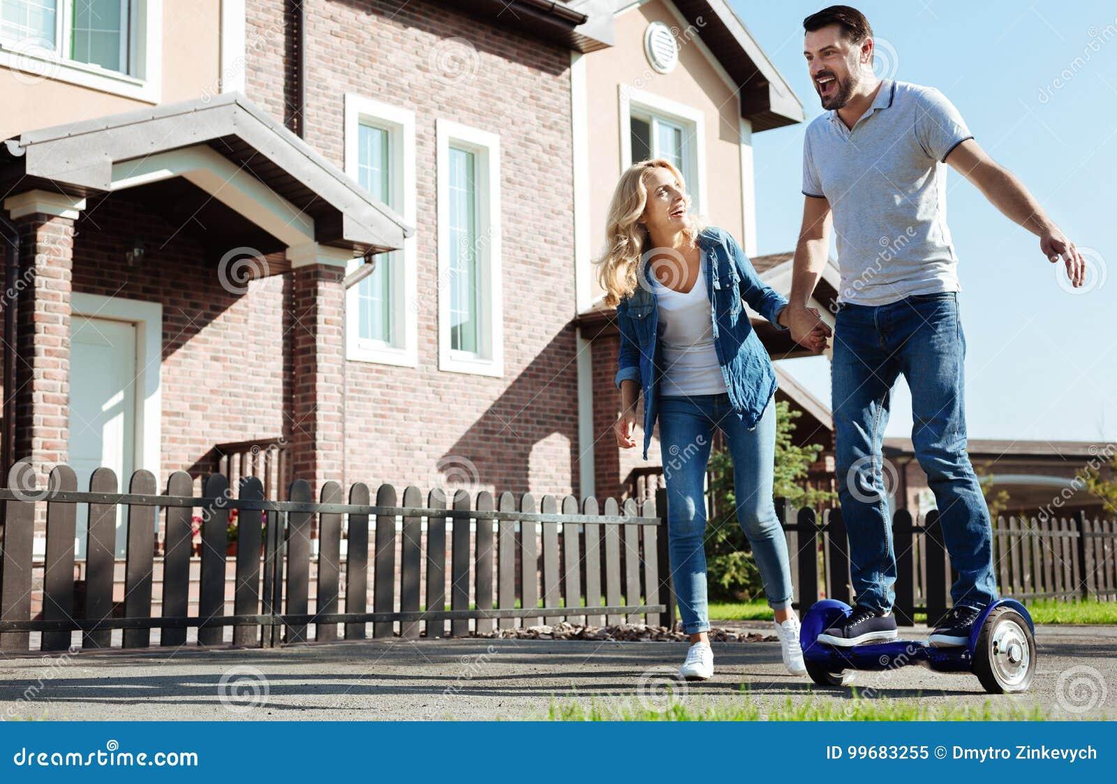 Hoverboard del montar a caballo del hombre y mano emocionados de los wifes de la tenencia