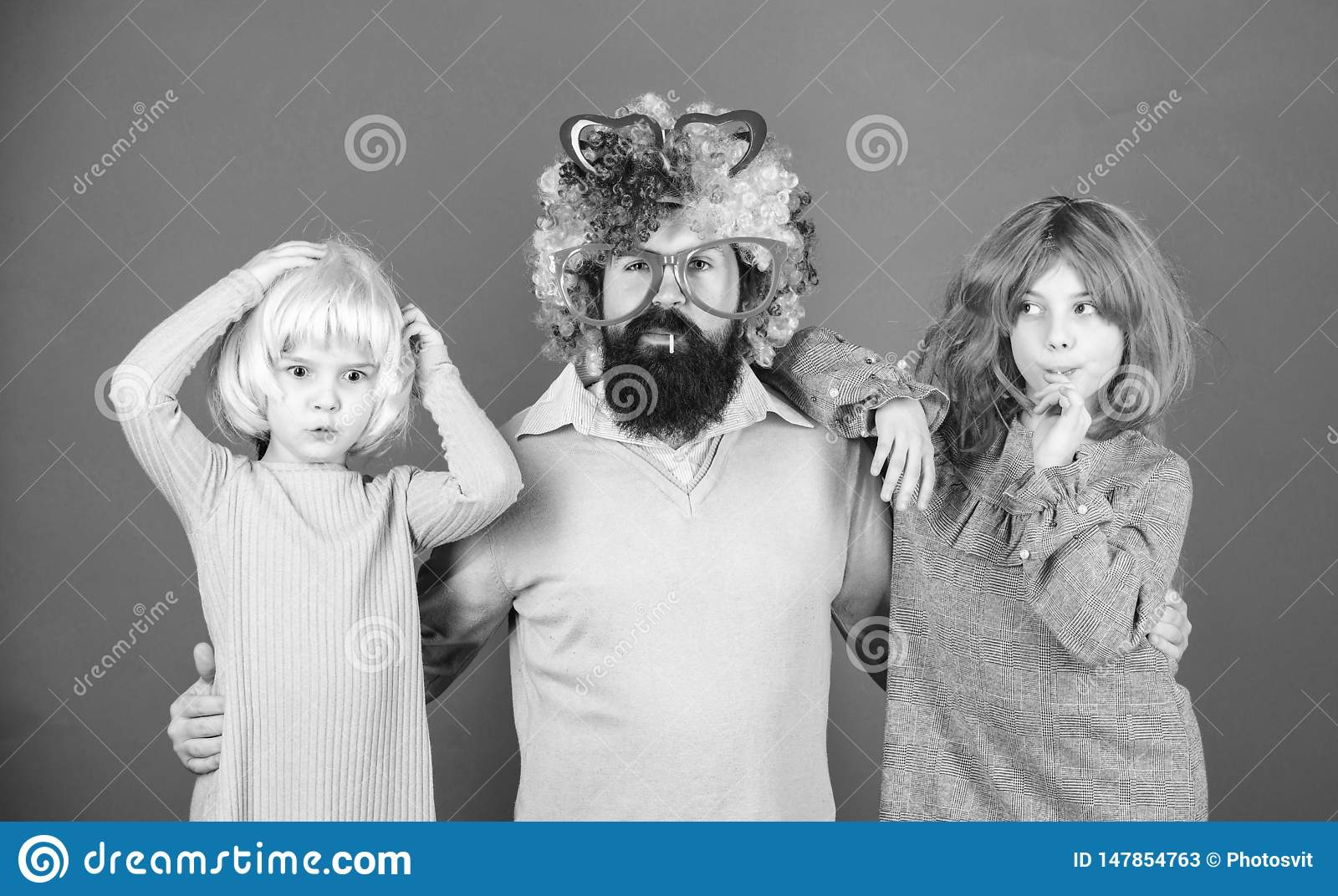 How crazy is your father. Man bearded father and kids girls wear colorful wig violet background. Friendly family wear