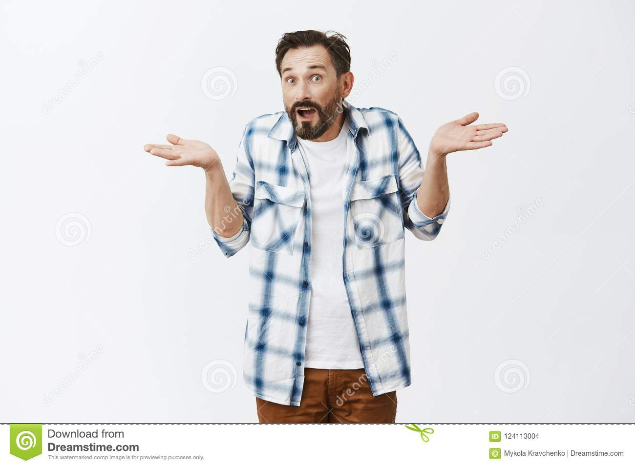 How should I know. Unaware confused adult guy with beard and moustache in casual checked shirt over t-shirt, shrugging