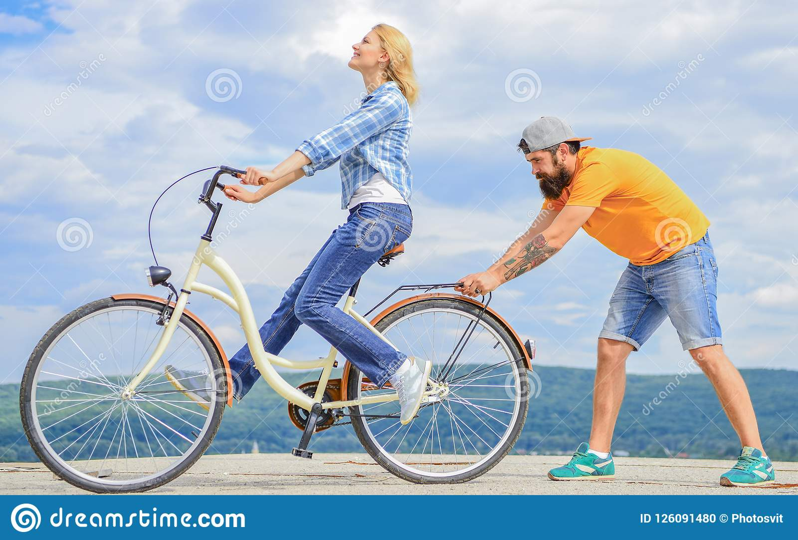 How to learn to ride bike as an adult. Girl cycling while boyfriend support her. Teach adult to ride bike. Man helps