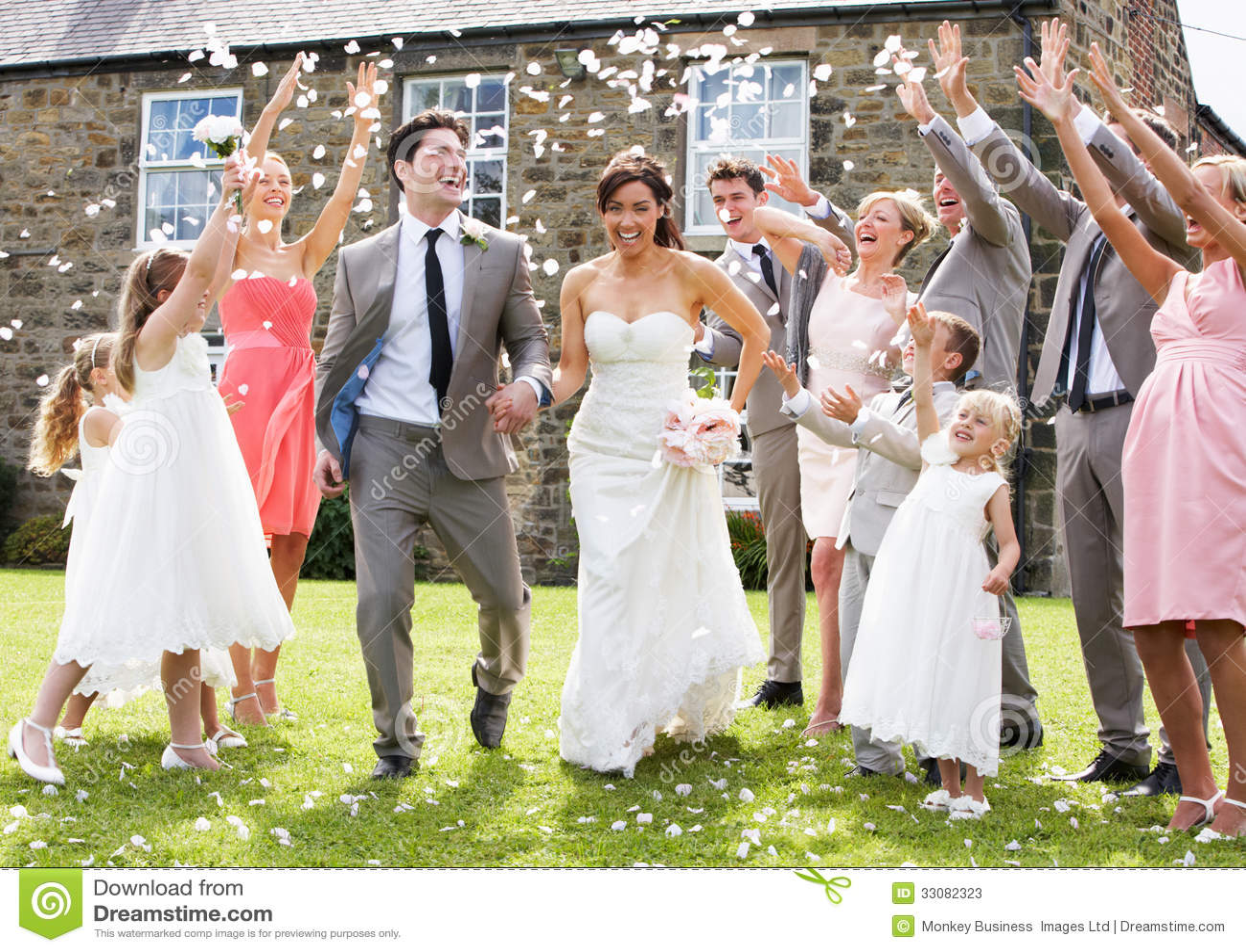 Huéspedes que lanzan confeti sobre novia y novio