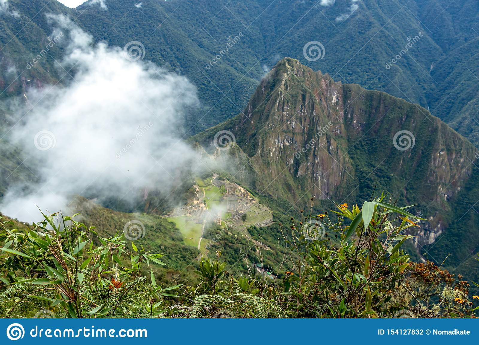 Huayna Picchu, or Wayna Pikchu, mountain in clouds rises over Machu Picchu Inca citadel, lost city of the Incas