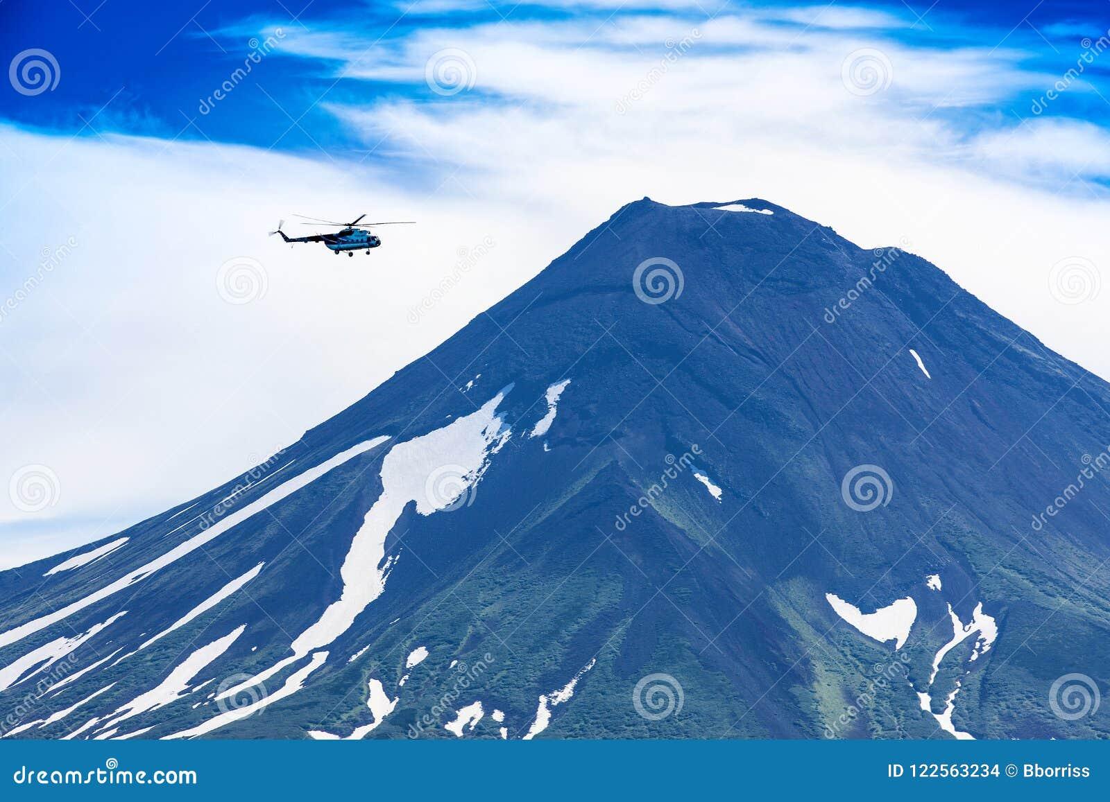 Hubschrauber, der über Ilyinsky-Vulkan und Kurile See fliegt