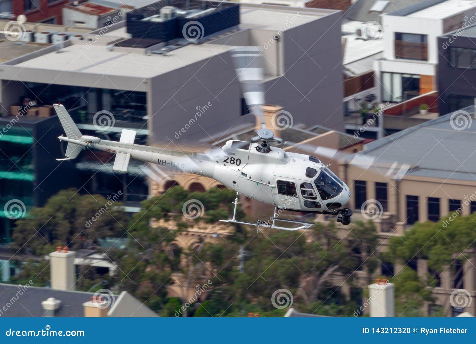 Hubschrauber Eurocopter AS-350BA, der Luftschmierfilmbildung mit einer Nase leitet, brachte Cineflex-Kamera über Melbourne an