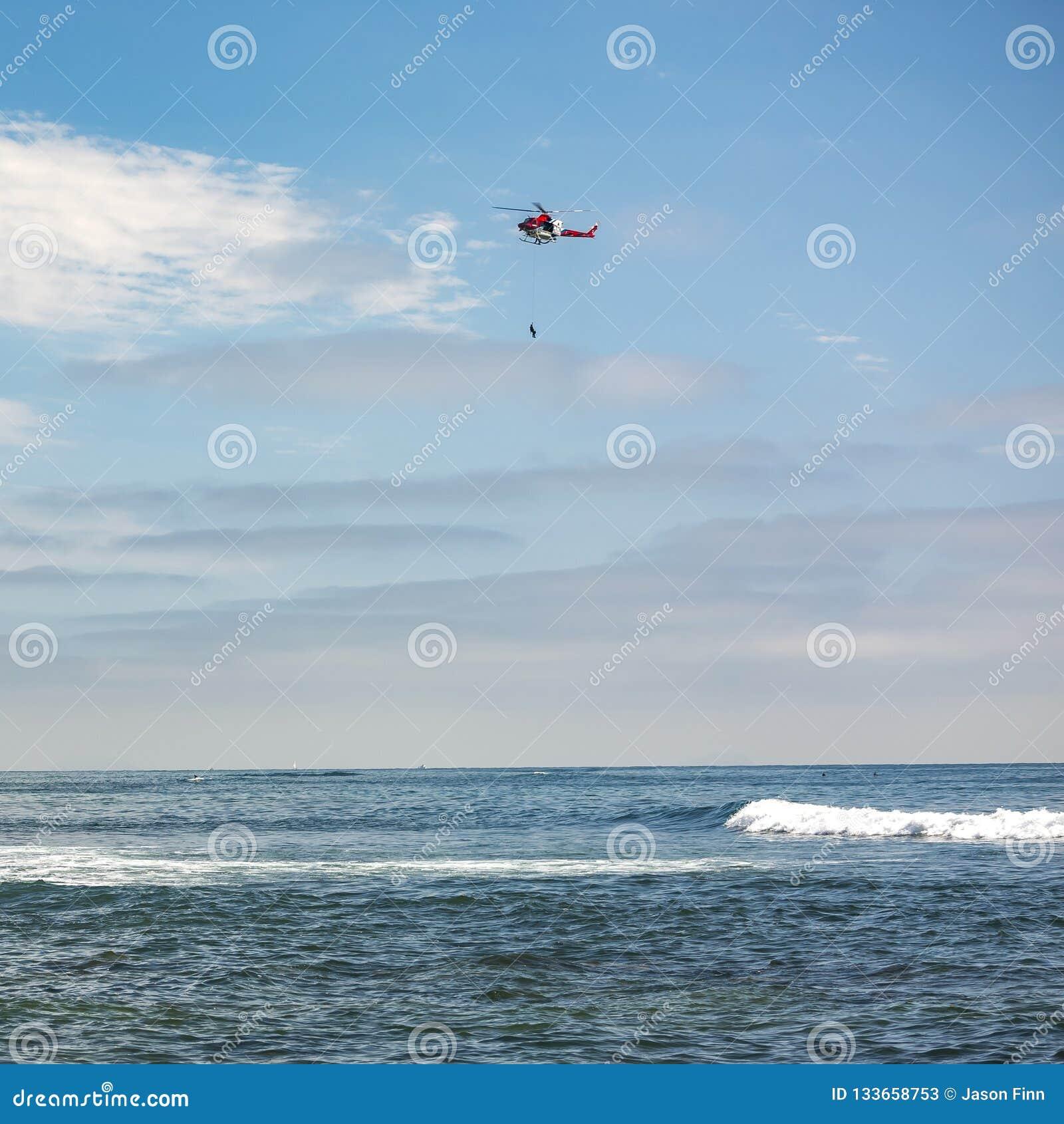 Hubschrauber mit hängender Person über La- Jollameer