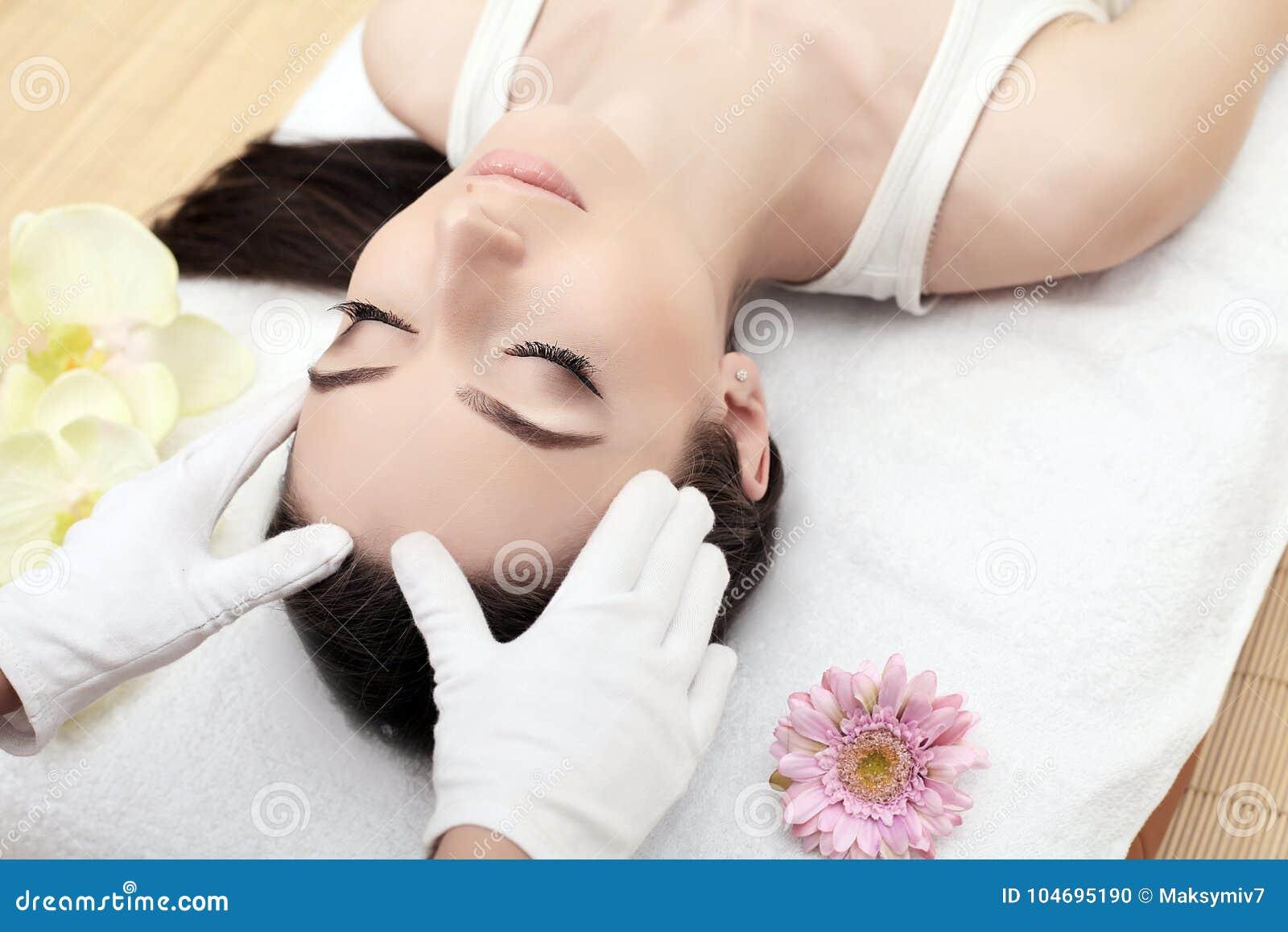 Hud och kroppomsorg Närbild av en ung kvinna som får Spa behandling på skönhetsalongen Spa vänder mot massage Ansikts- skönhetbeh