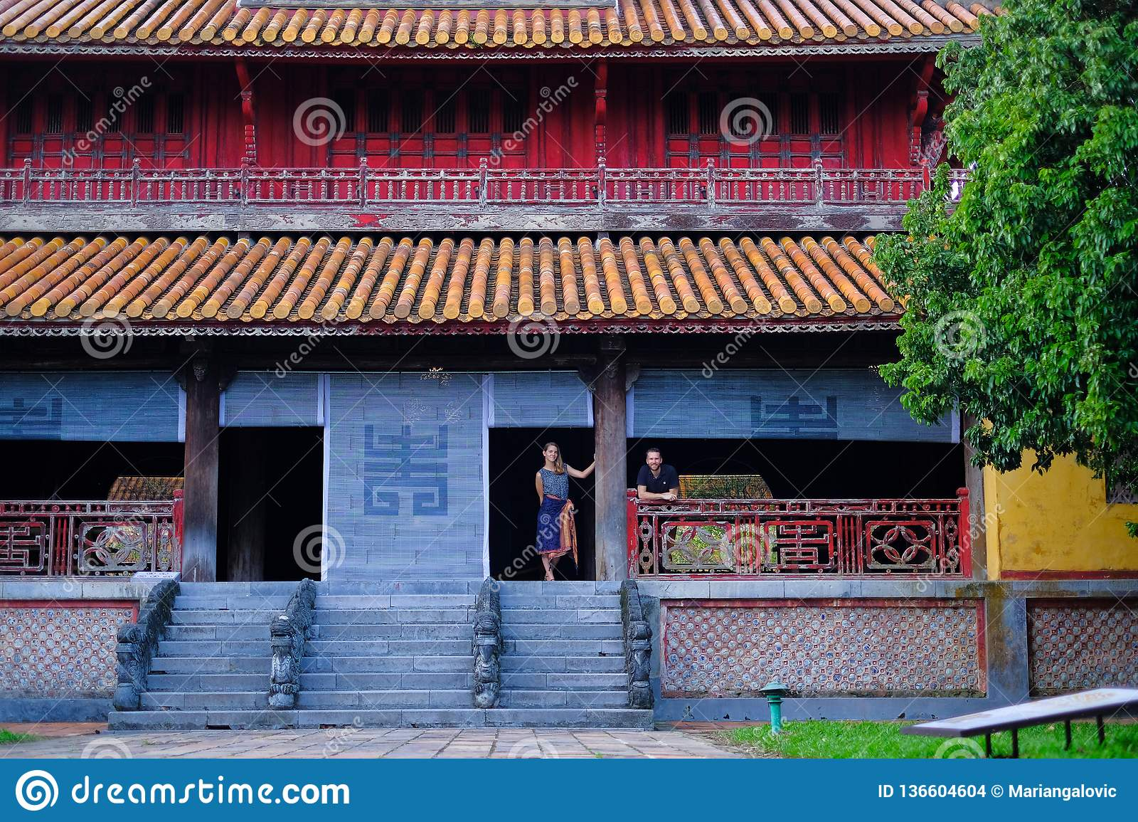 Hue / Vietnam, 17/11/2017: Couple standing inside a traditional house with ornamental tiled roof in the Citadel of Hue, Vietnam