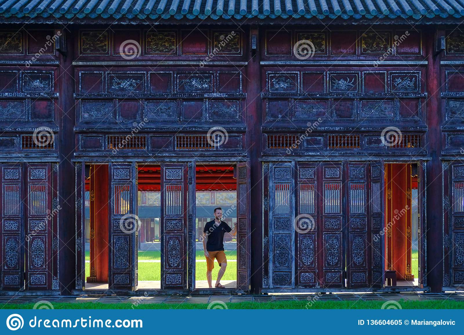 Hue / Vietnam, 17/11/2017: Man standing next to ornamental doors in a traditional pavillion in the Citadel complex in Hue,