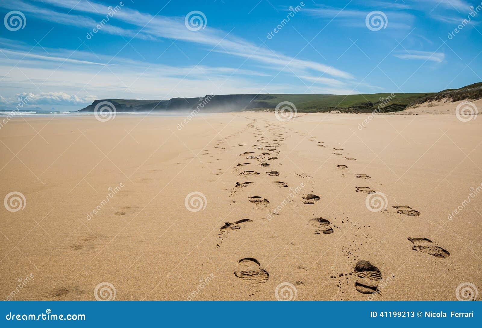 Huellas de caminar botas en la arena de una playa remota for Arena de playa precio
