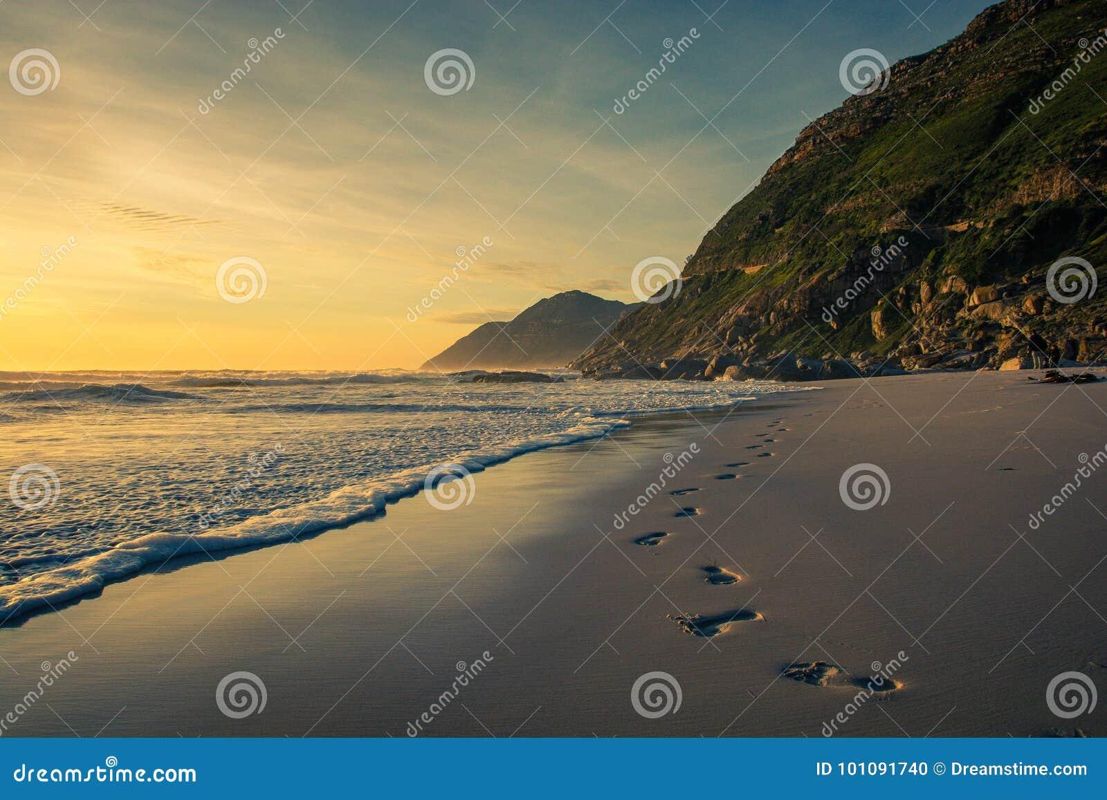 Huellas en la arena en la puesta del sol