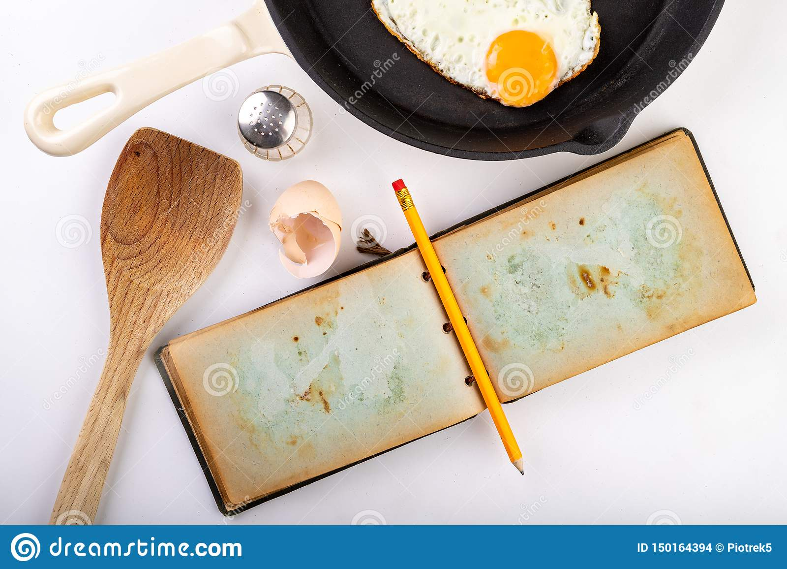 Huevo frito asty en una sartén del arrabio  Preparación de un desayuno sabroso según la receta de un cuaderno viejo