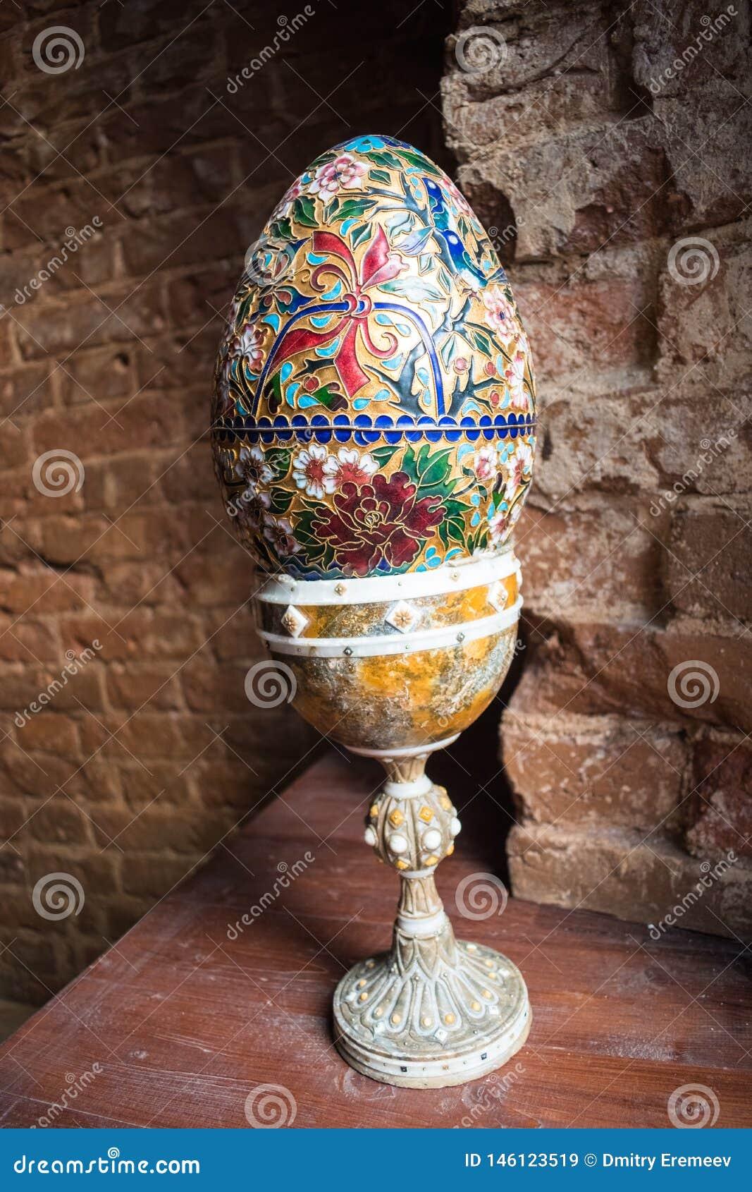 Huevo pintado grande en un soporte en un fondo del ladrillo rojo