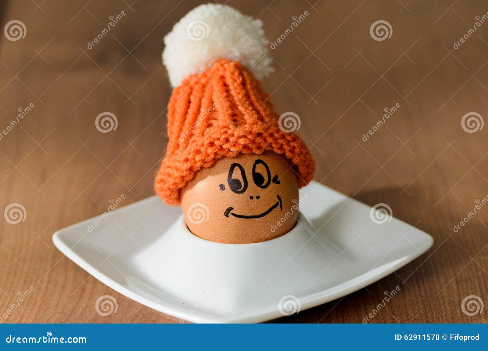 Huevo sonriente con el capo hecho punto que se sienta en la huevera blanca