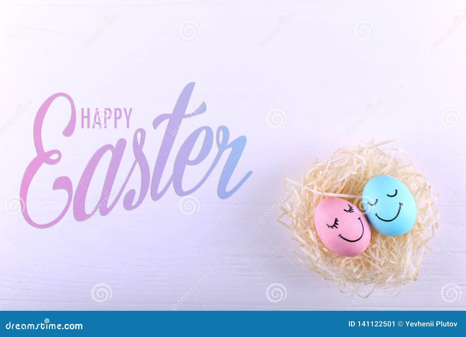 Huevos azules y rosados con sonrisas pintadas en la jerarquía, espacio de la copia Diseño feliz de la tarjeta de felicitación del