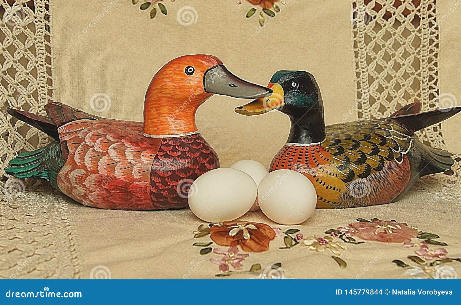 Huevos blancos de Pascua al lado del pato en fondo beige