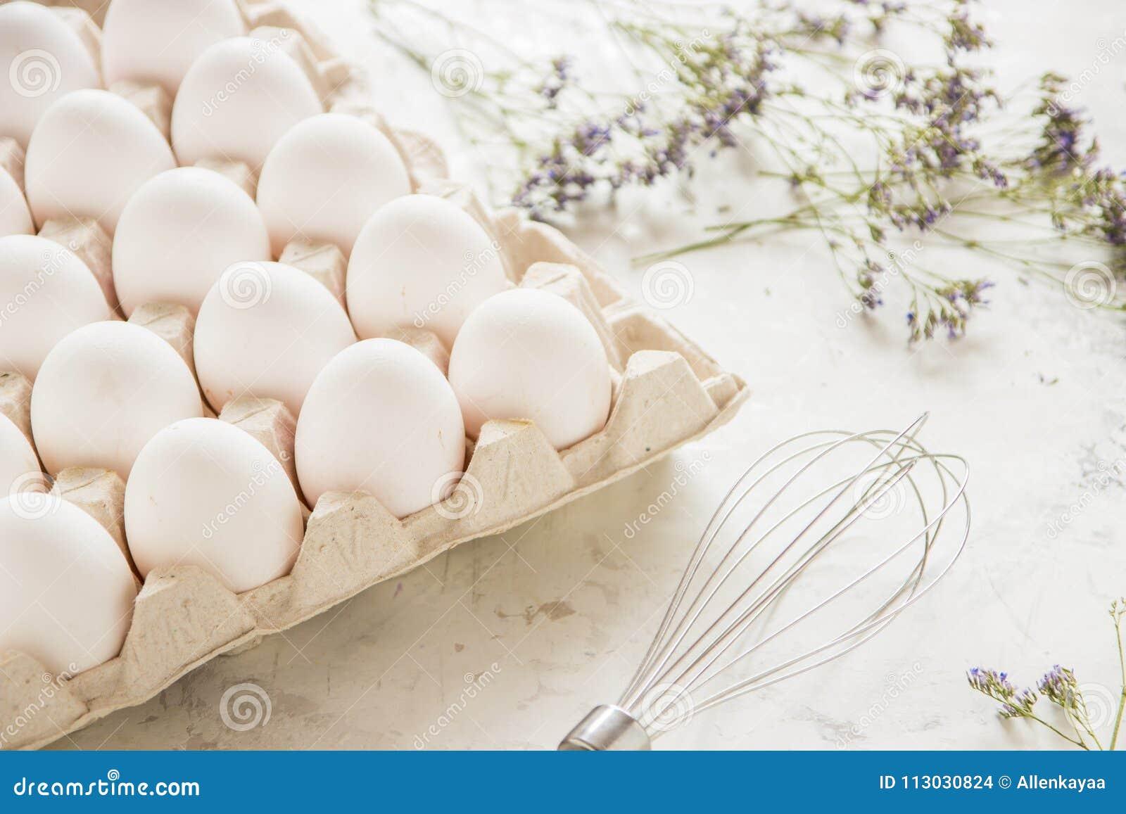 Huevos blancos en una caja en un fondo ligero
